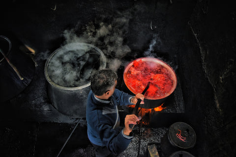 A man in black background making red colour with natural vegetable dyes