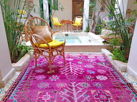 A room with a pink carpet, a wooden chair with yellow pillow