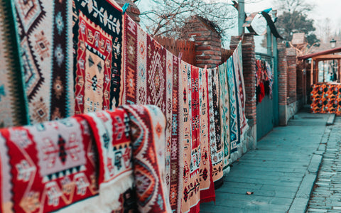 Handmade carpets hung on a wall with lots of colours