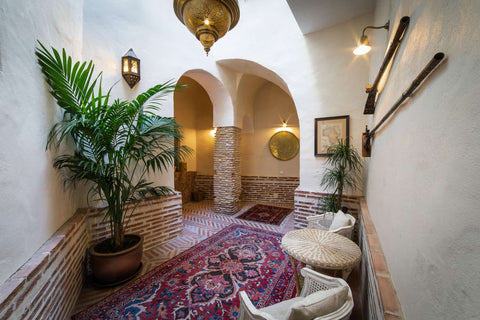 A hallway with arches, white walls, a palm tree and a handmade carpet