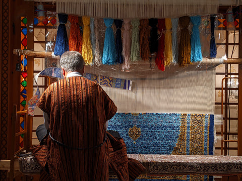A man making a handmade carpet with various colours