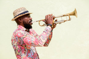 A man wearing a Panama hatand wearing a pink pasley long sleeve shirt. He is playing the trumpet. Plain beige wall background