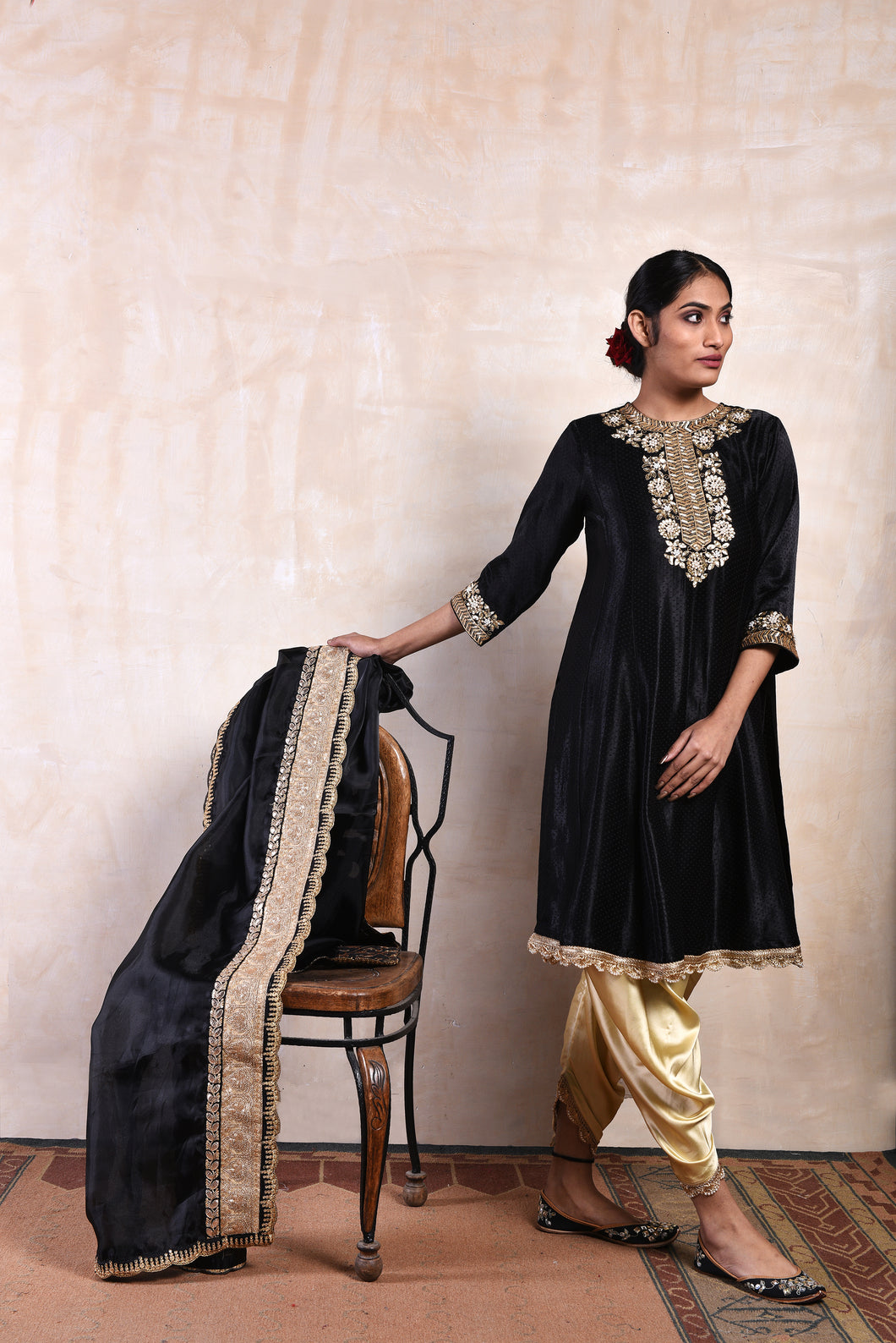 A Line Black Short Shaneel Kurta and Dupatta. Offset by a Pair of Gold Tulip Pants Complimenting the Gold Zari Work.