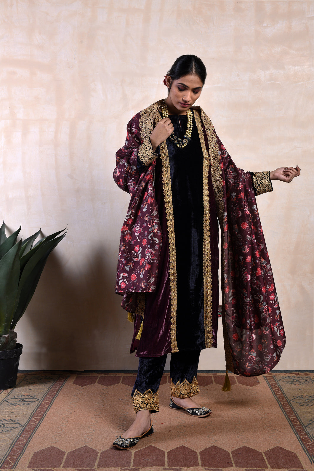 A straight kali kurta in ink blue and purple velvet paired with a choti mori velvet salwar and a floral dupatta