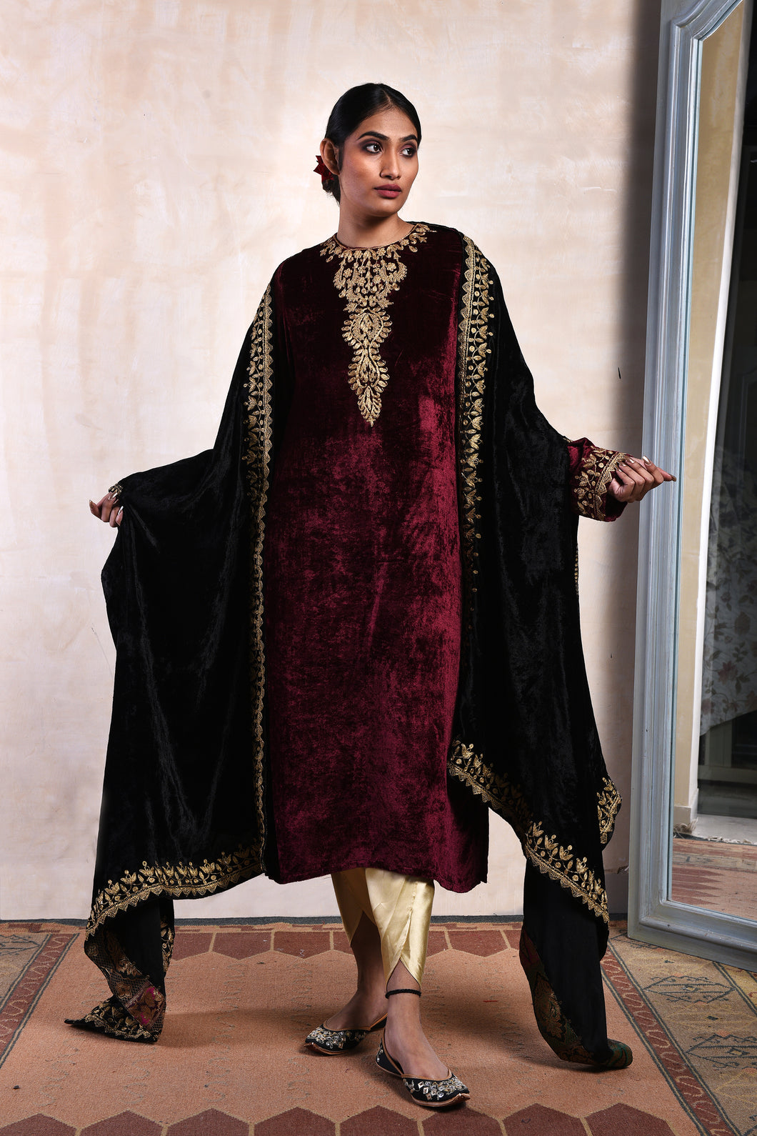 A burgundy Velvet zari kurta with a black zari shaneel odhni. Rich gold satin tulip pants