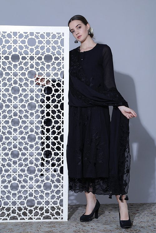 An A line black suit with high slits and tonal thread work, dupatta and pallazo with embroidered borders on organza.