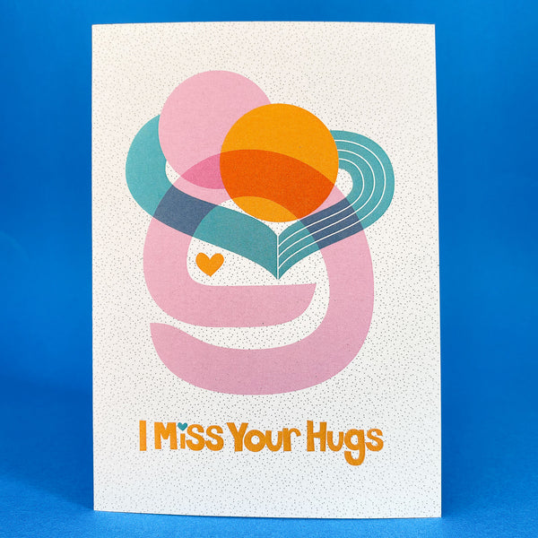 I Miss your Hugs Card on a blue background stood open.