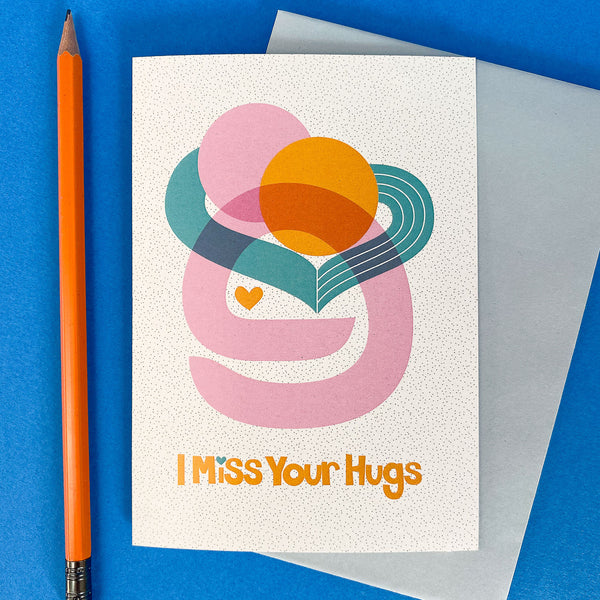 I Miss your Hugs Card on a blue background with orange pencil.