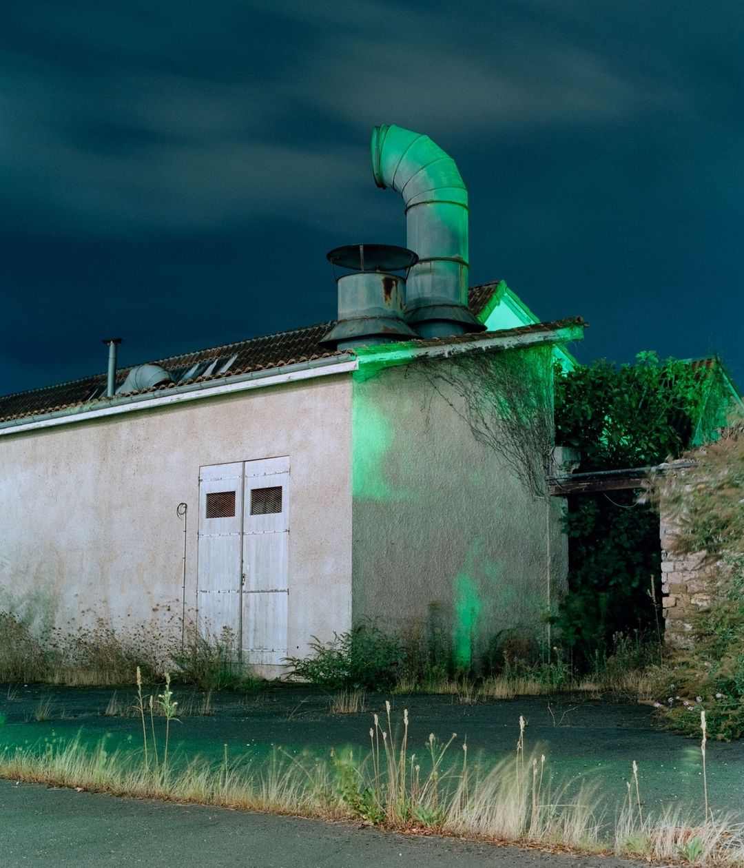 night time shot of a house with green light