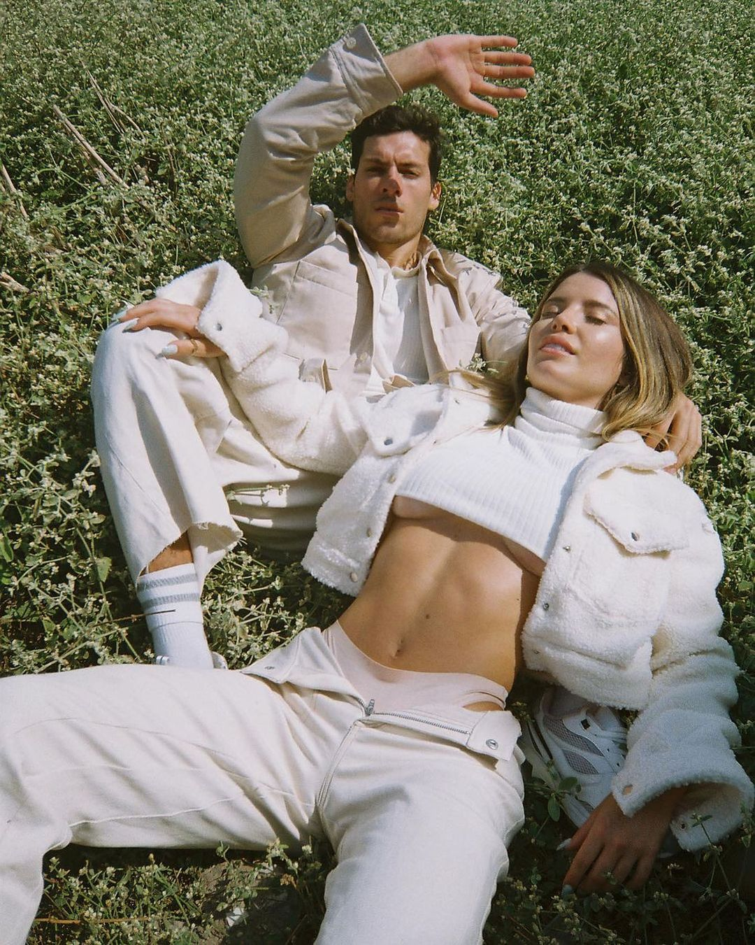 a couple of models lay in the grass