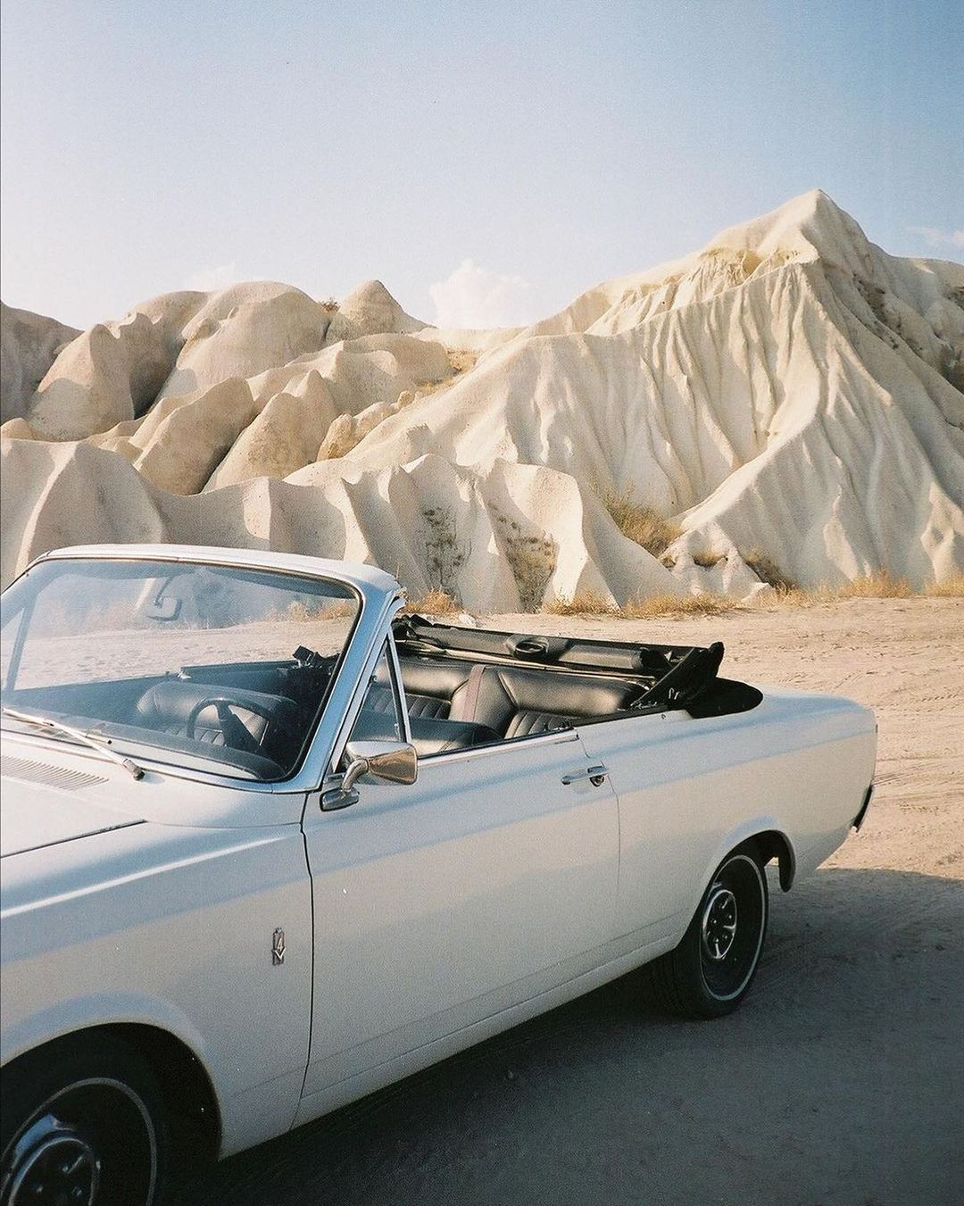 35mm film photo of a white car in the desert