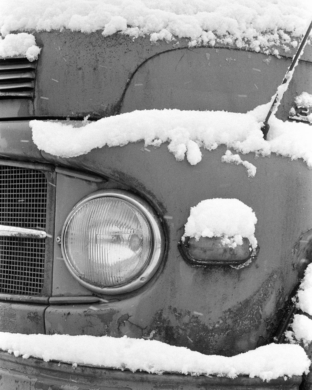 black and white film photo of a car covered in snow