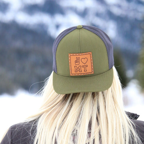 Model wears a forest green trucker hat backwards. There is a leather patch sewn on with peace fingers, a heart, and MT engraved. A frozen lake and mountains are featured in the background.