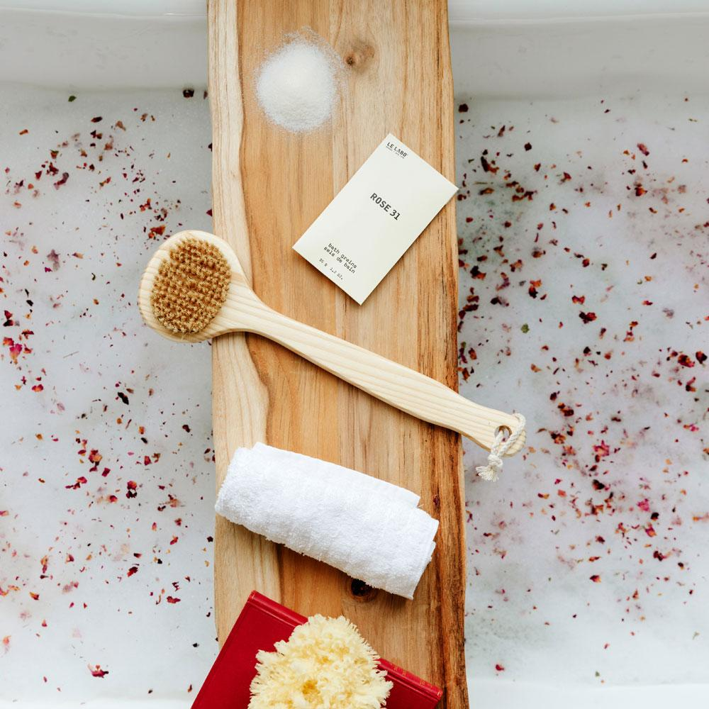 Le Labo Rose 31 Bath Salts on tray in bath tub with rose petals
