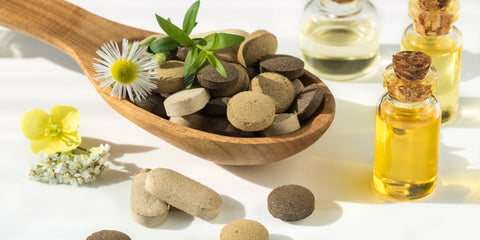 Herbal supplements in a wooden spoon and herbal oils in small glass jars.