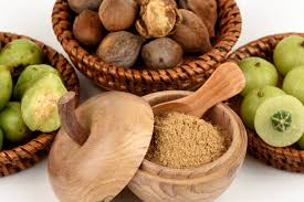 Three different superfoods in separate woven baskets and a bowl of triphala powder