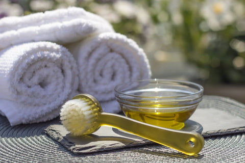 Rolled towels, a bowl of massage oil and a massage brush on a table.