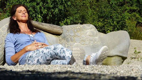 A woman sitting reclined on gravel in the sun.