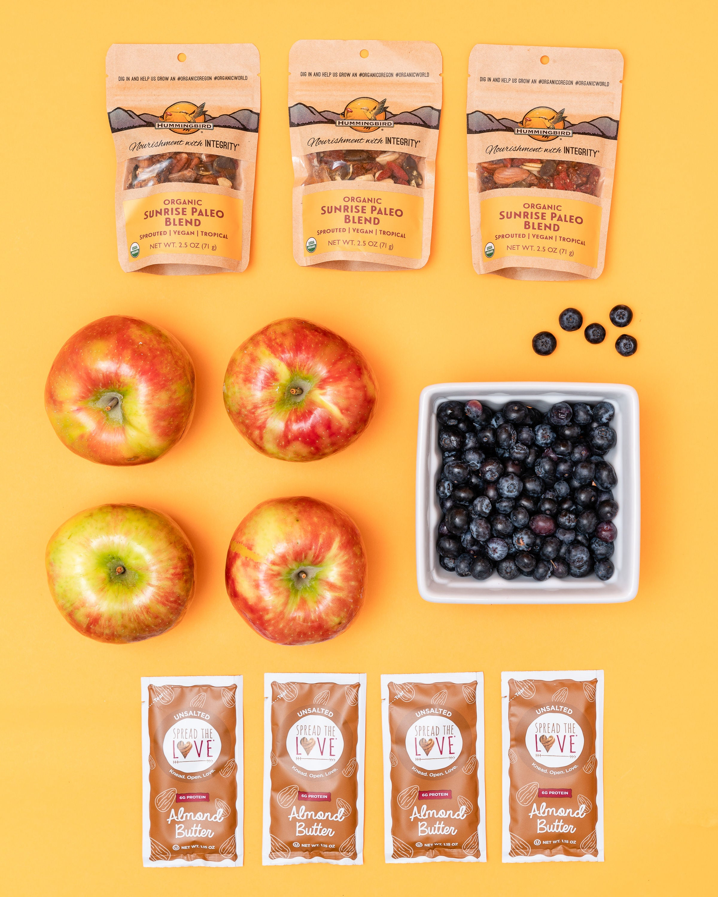 healthy snack fruit box with apples, blueberries, nuts, and almond butter