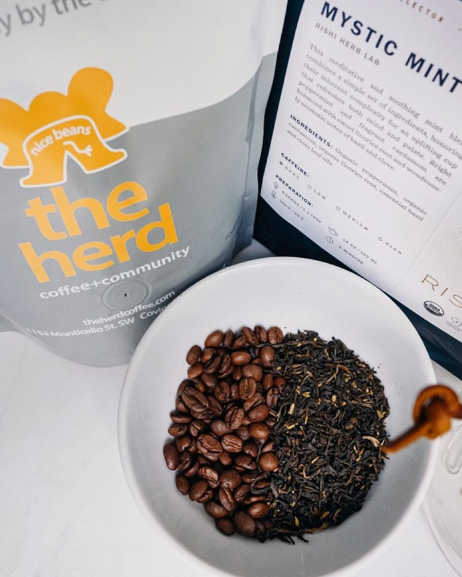 Coffee beans and herbs in a white bowl on a counter
