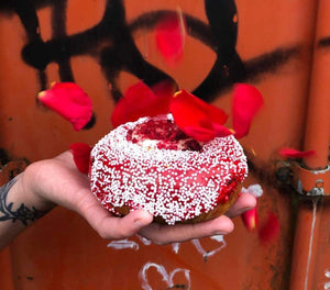 Red velvet, raspberry and vanilla vegan donut with red rose petals falling.