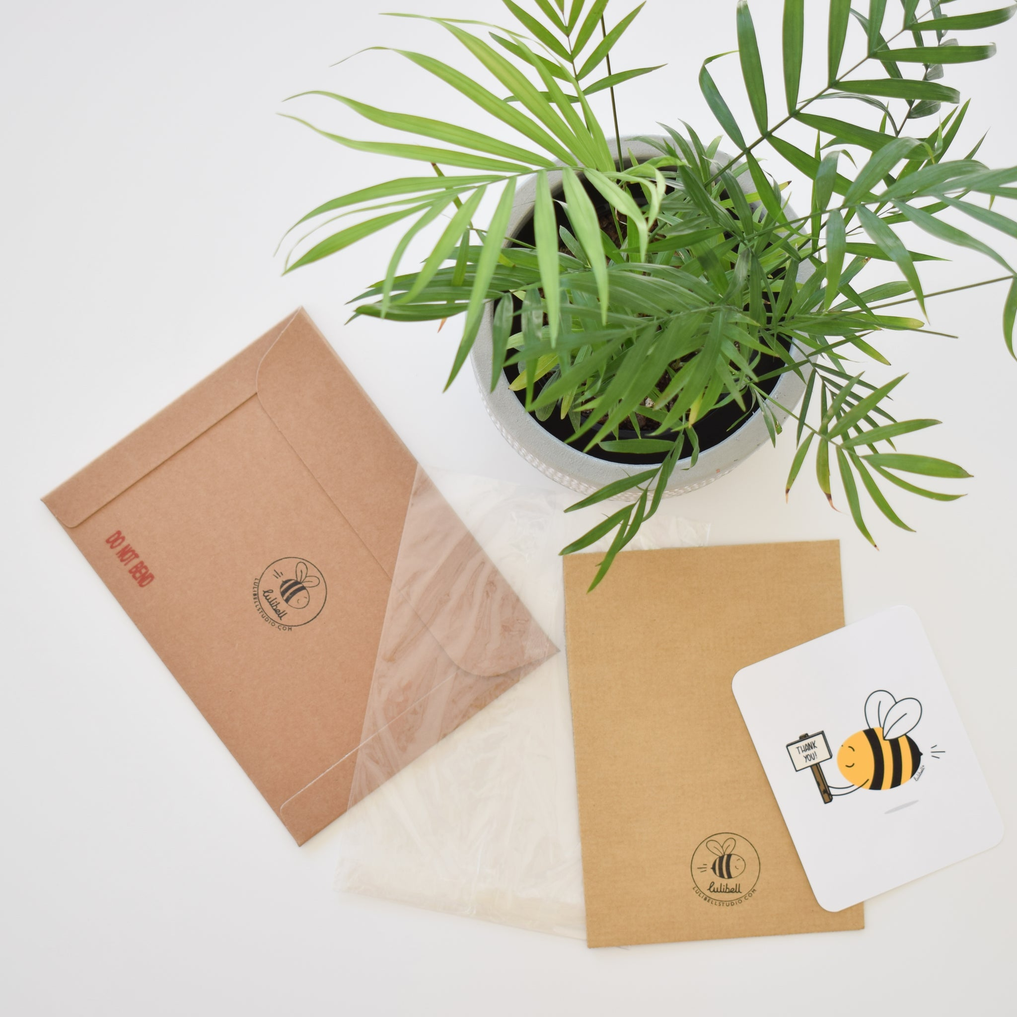 Flat lay photograph of Lulibell Studio eco friendly packaging - brown rigid mailer envelope with logo and 'do not bend' stamp, clear cellophane bag, backing board with stamp, thank you card featuring a bee holding a sign saying 'thank you'.