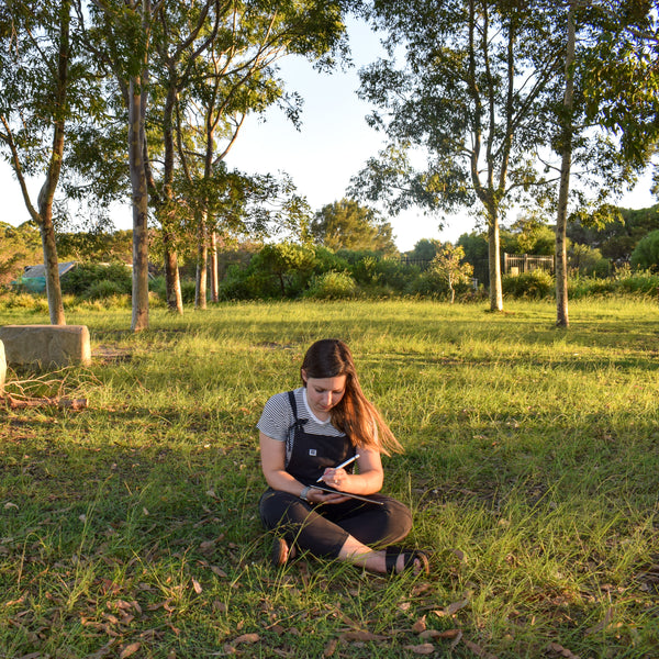 Photograph of Lieha, the illustrator behind Lulibell Studio. Lieha is wearing a stripey tshirt, black dungarees and sandals. She has brown and blonde hair. She is sitting on the grass between some trees, drawing on an iPad.