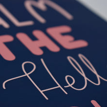 Load image into Gallery viewer, A close up photograph of our 'Calm The Hell Down' print on a white wall in a white frame - hand lettered text that reads 'calm the hell down' in shades of pink on a navy blue background.