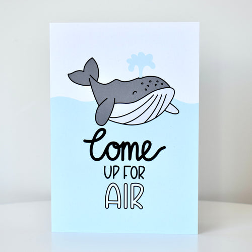 Greetings card featuring an illustration of a grey humpback whale with water shooting out of its blowhole, a blue wave in the background, with hand lettering that reads 'come up for air', by Lulibell Studio.