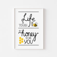 Load image into Gallery viewer, A photograph of our Life Is Tough print on a white wall in a white frame - Hand written text in a variety of styles in black ink that reads 'Life is tough but honey so are you'. Also includes illustrations of a bee holding a sign that says 'you got this!' and a honeycomb.