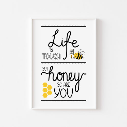 A photograph of our Life Is Tough print on a white wall in a white frame - Hand written text in a variety of styles in black ink that reads 'Life is tough but honey so are you'. Also includes illustrations of a bee holding a sign that says 'you got this!' and a honeycomb.