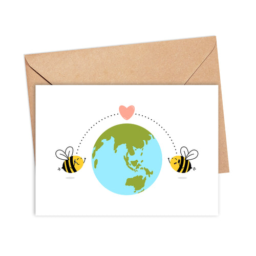 Greetings card featuring an illustration of two bees on phones on either side of the planet, with dotted lines between them and a heart, by Lulibell Studio.