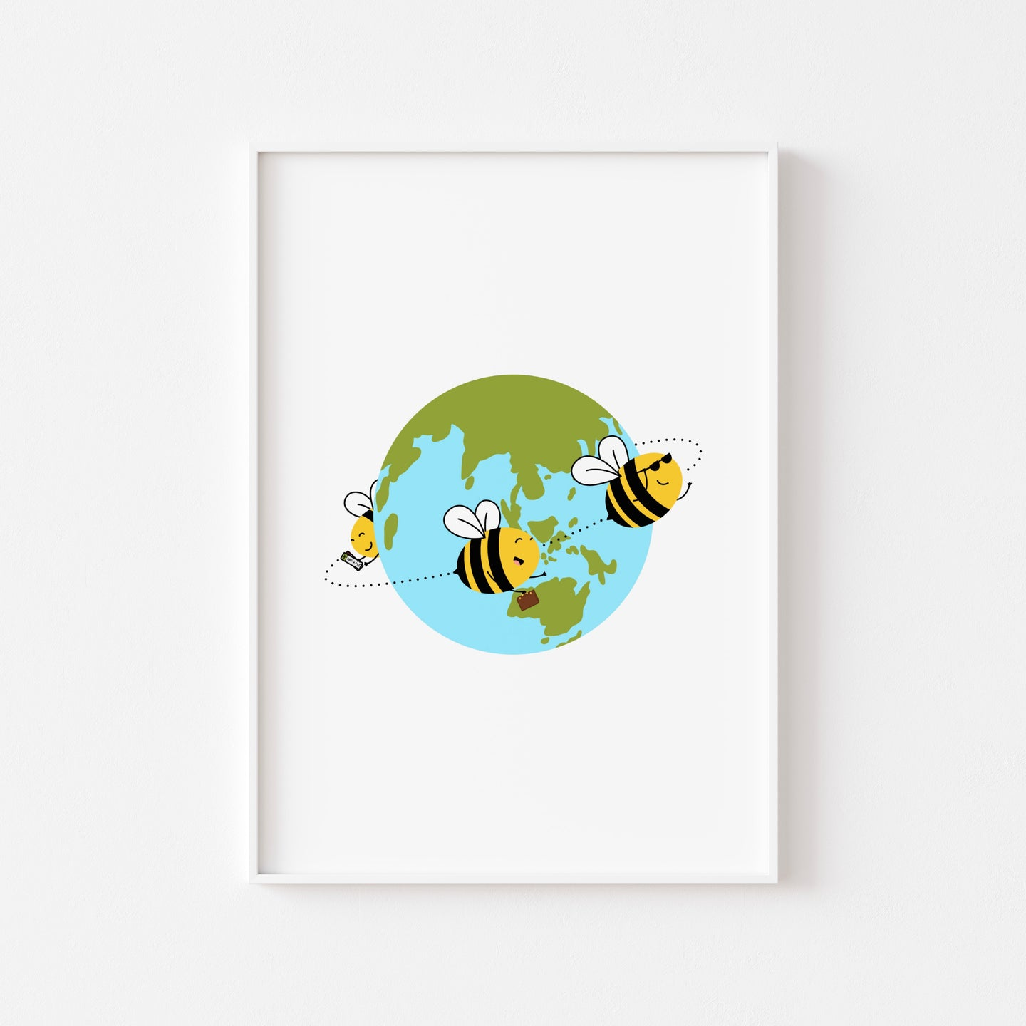 A photograph of our Travelling Bees print on a white wall in a white frame - three bees flying around the world - one holding tickets, one holding a suitcase, one wearing sunglasses, by Lulibell Studio.