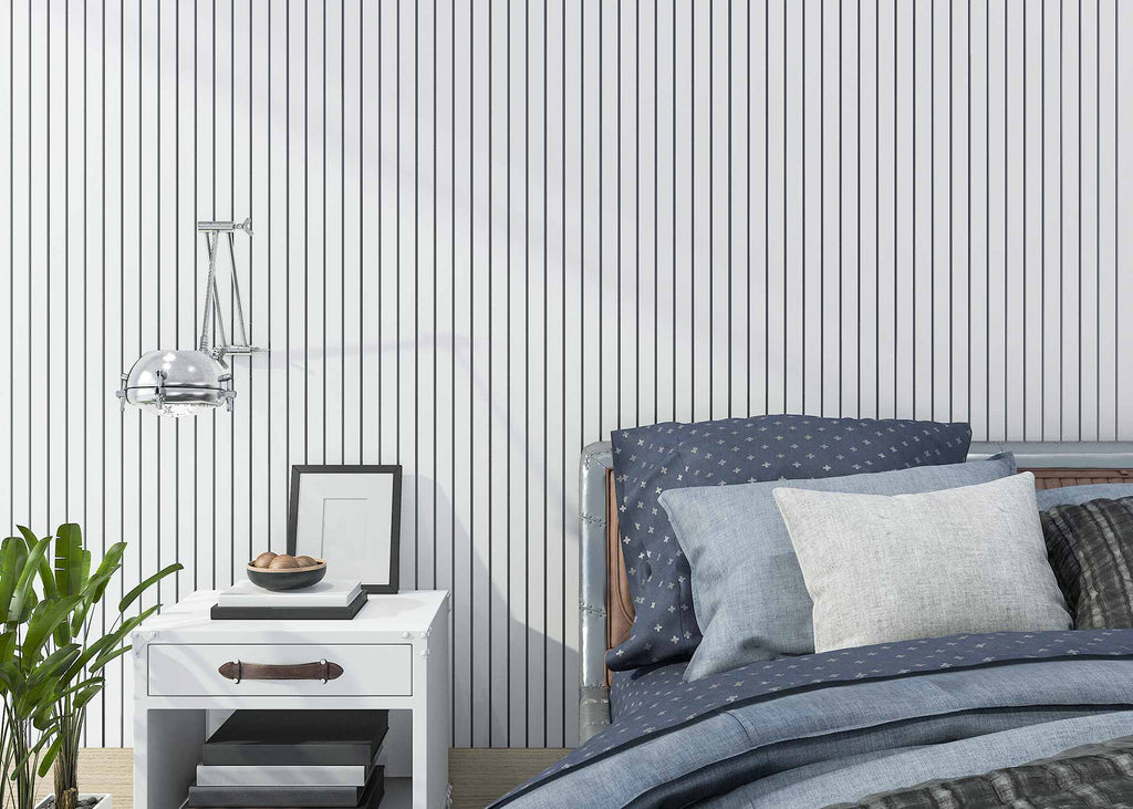 room with striped wallpaper, bed with blue sheets and pillows, and white small table
