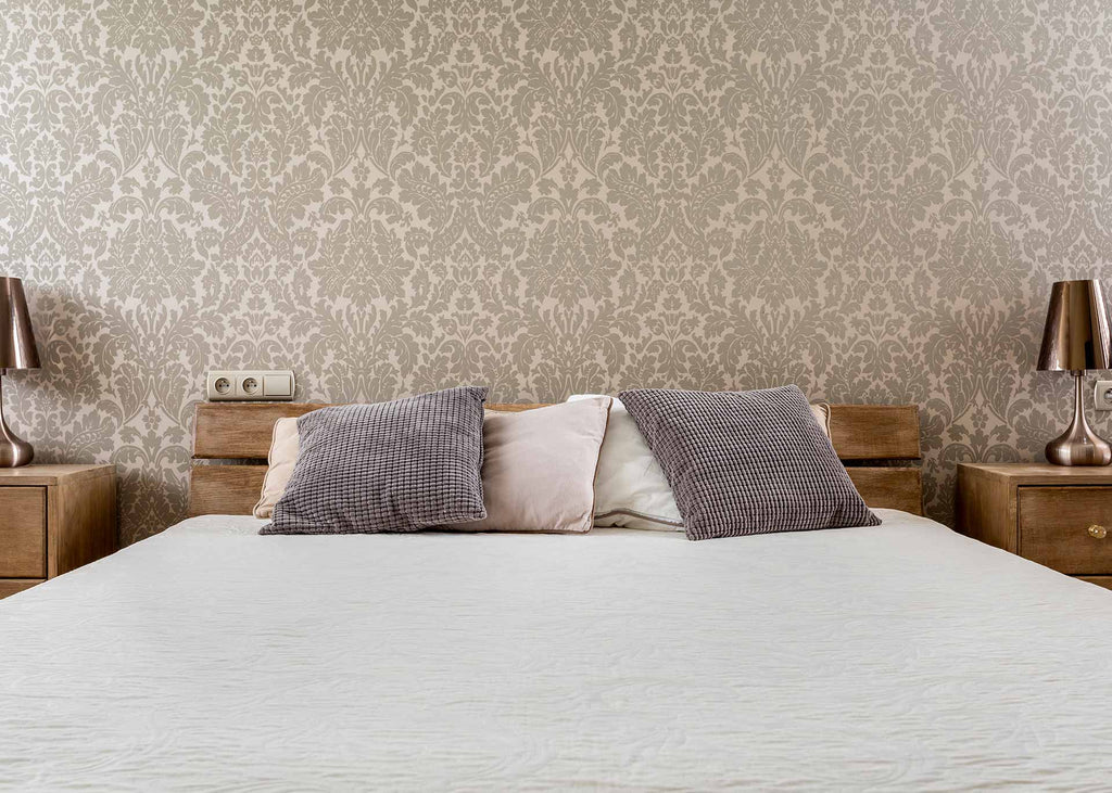 room with ornate wallpaper and bed with pillows and sheets with muted colours
