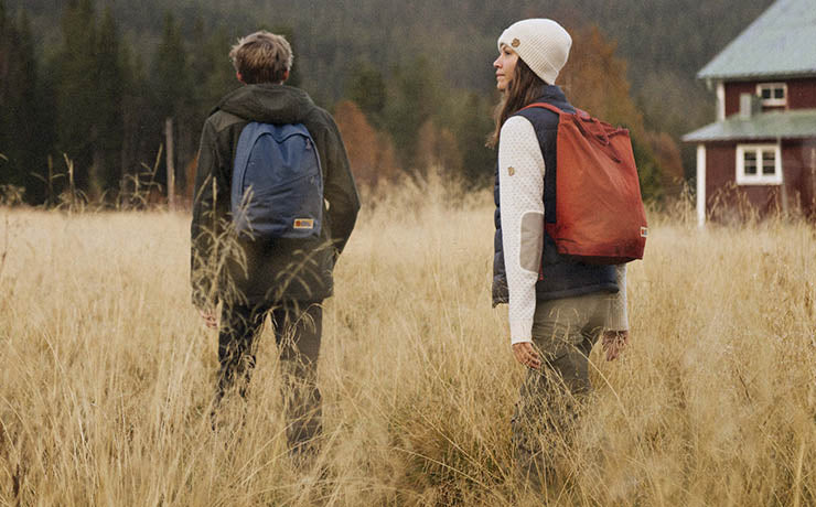 Man Trekking with Fjallraven Shoulder Bag and Wearing Cap and Blue T-Shirt