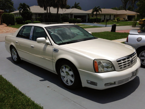 A clean and detailed exterior photo of a pearl white 2005 Cadillac Deville