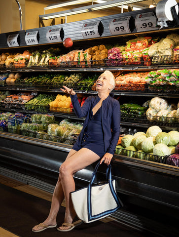 Jane at grocery store in navy surf shirt and board shorts