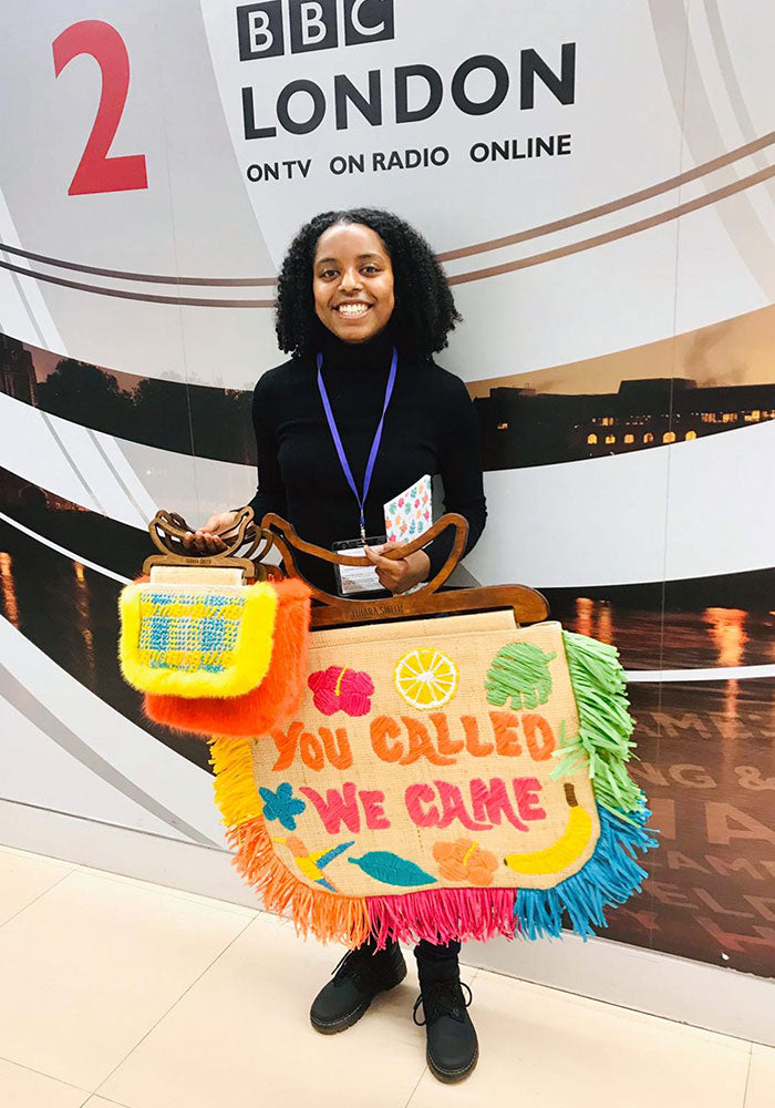 Image of Tihara Smith holding raffia bags in front of a BBC Radio London sign