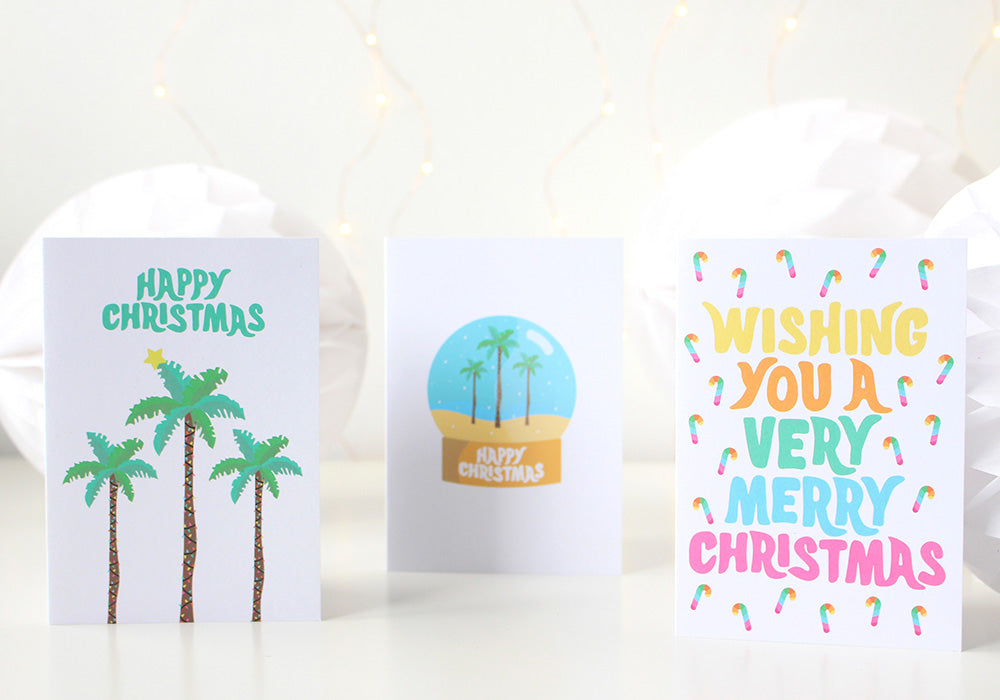 Image of three tropical Christmas cards standing beside each other