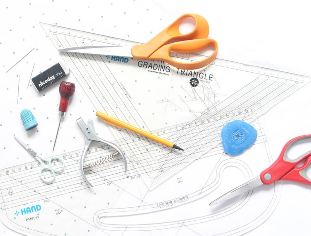 Creative pattern making equipment displayed on a table with scissors, pins, thimble, erasure and rulers