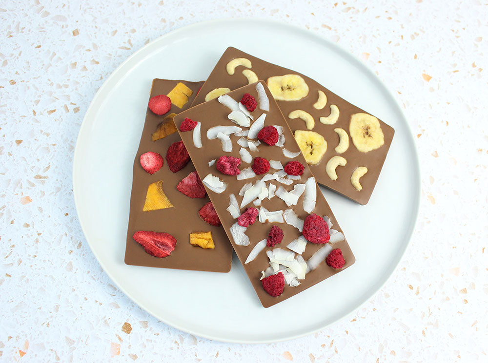 Image of three chocolate bars on a white plate with different fruit toppings.