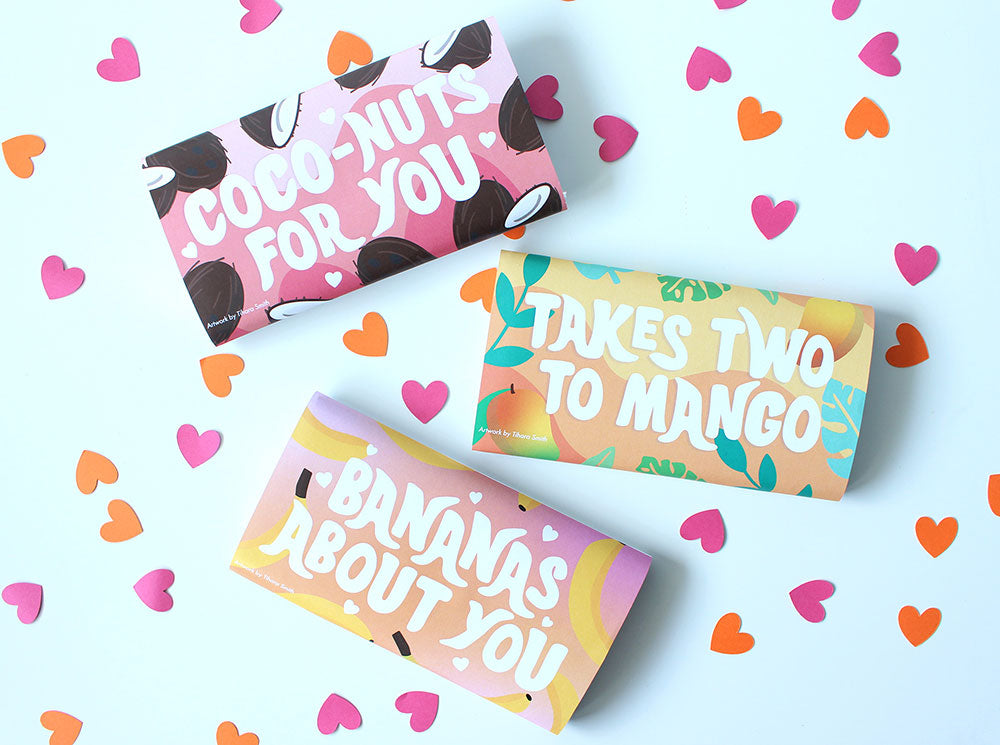 Image of three wrapped chocolate bars on a white table with scattered heart confetti