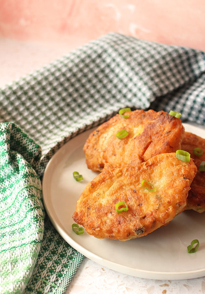 Image of saltfish fritters on a white place with a green tea towel beside it