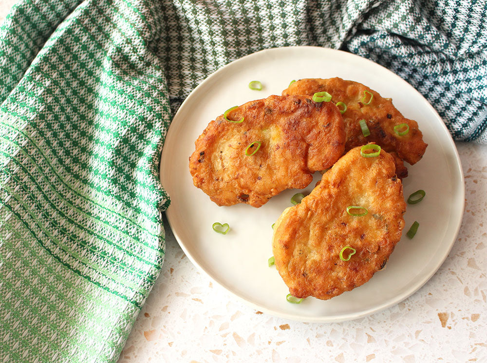Image of saltfish fritters on a white plate with a green tea towel beside it.