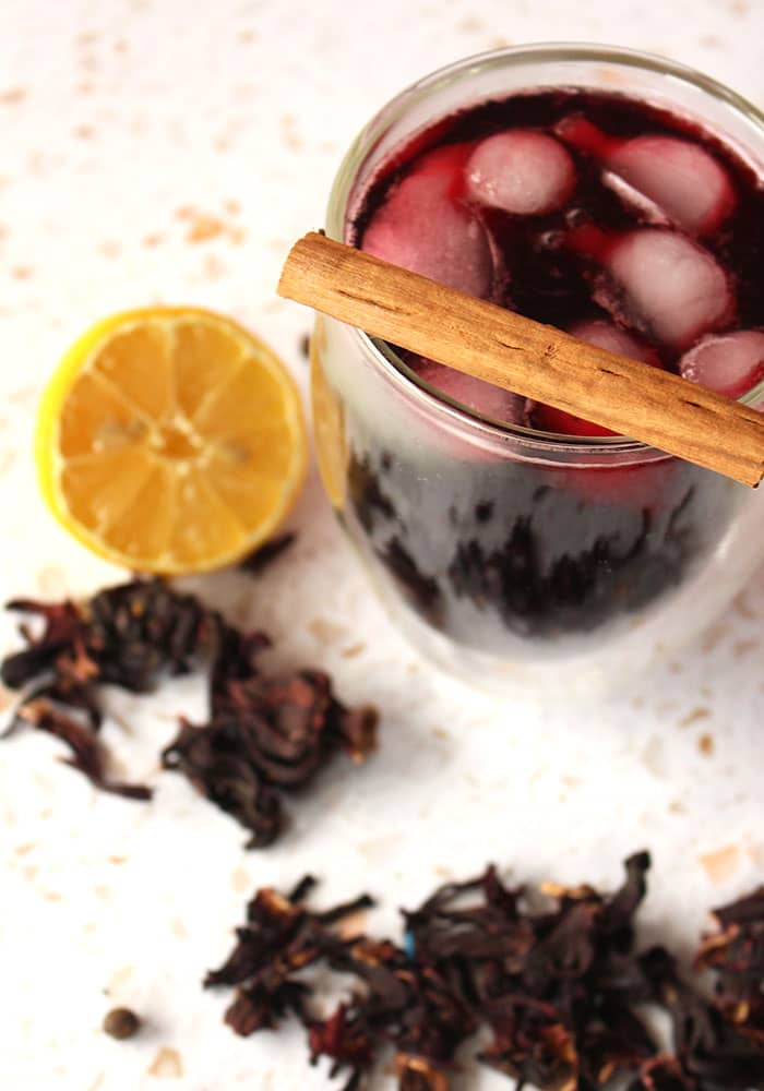 Image of a glass of sorrel drink with a cinnamon stick resting on top of the glass, and a half slice of lemon beside the glass along with some dried hibiscus flowers.