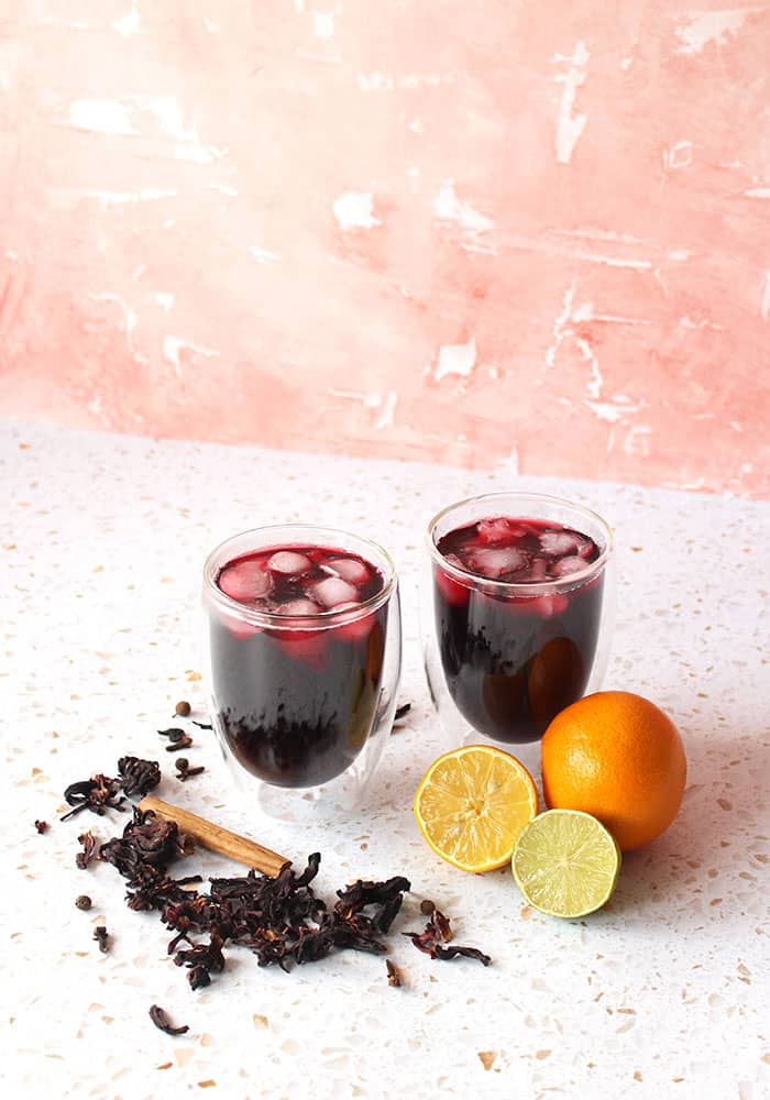 Image of two glass cups of sorrel drink with an orange, lemon and lime beside them.