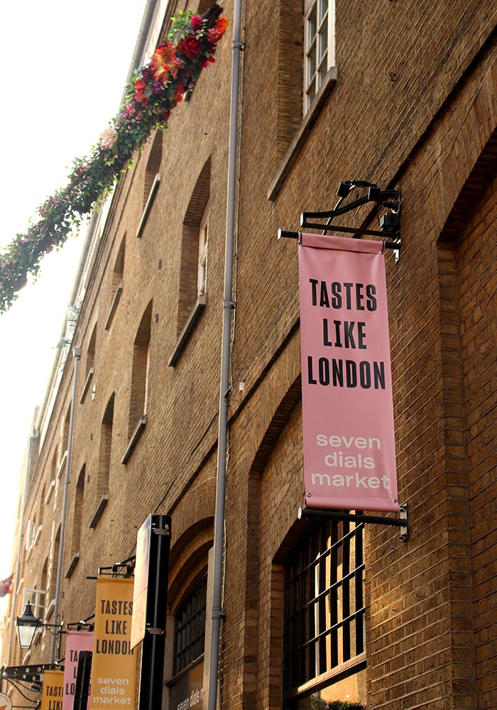 Image of Seven Dials Market building with a pink 'Tastes Like London' banner hanging from the building