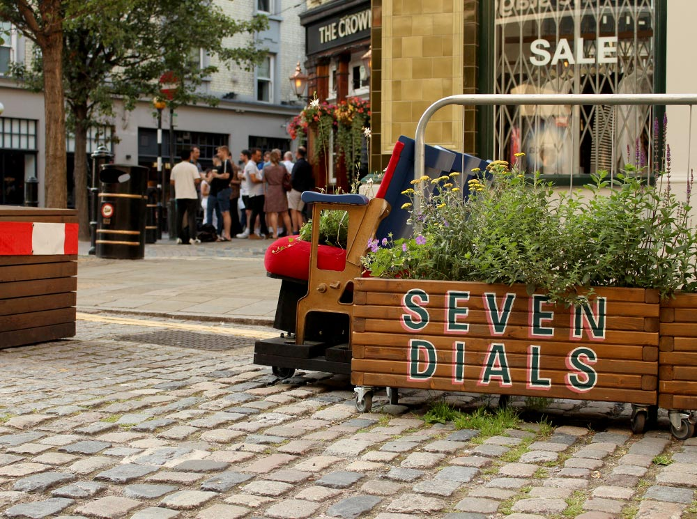 Image of cobbled road in Seven Dials with a wooden rectangular plant pot with 'Seven Dials' painted on it.