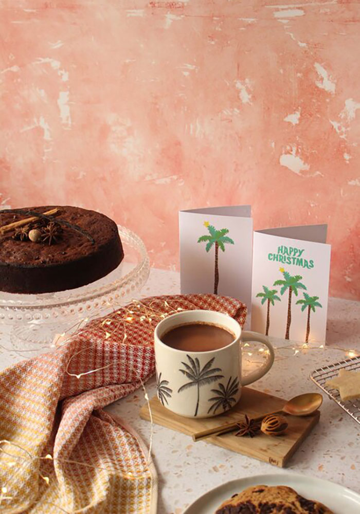 Image of cocoa tea on a table with a rum cake and fairy lights